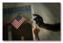 Hand holding small American flag reaching out to hand of marble statue