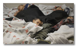 Children sleeping under Rec Cross blankets at border