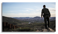 Border patrol officer surveying town from nearby hill